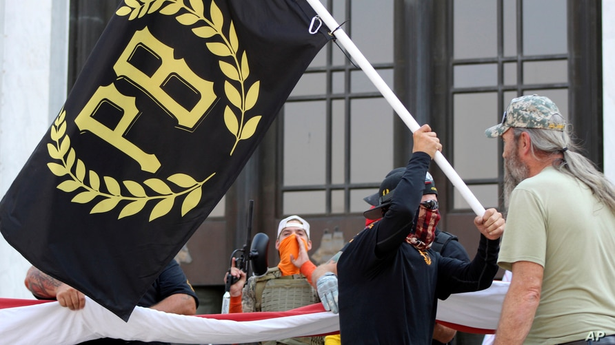 A protester carries a Proud Boys banner, a right-wing group, while other members start to unfurl a large U.S. flag in front of…