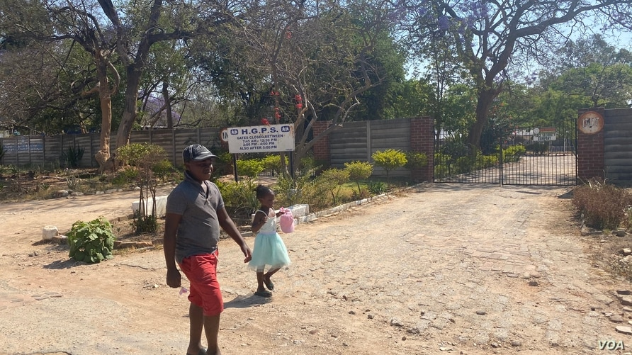 Children walks past the gate of school closed in Harare on September 22, 2020 (C. Mavhunga/VOA)