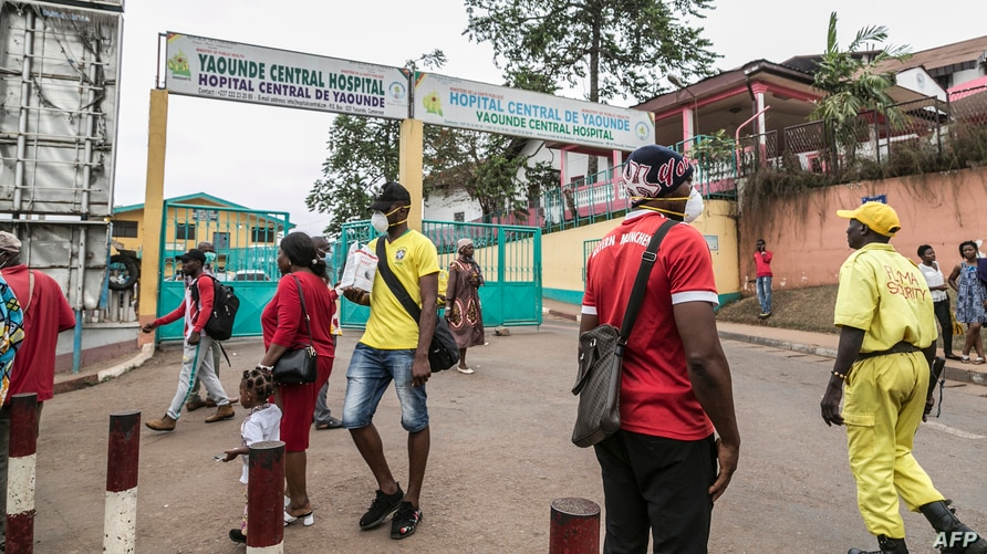 FILE - People, some wearing masks, walk by the entrance to Yaounde General Hospital, in Yaounde, Cameroon, March 6, 2020, amid the coronavirus pandemic.