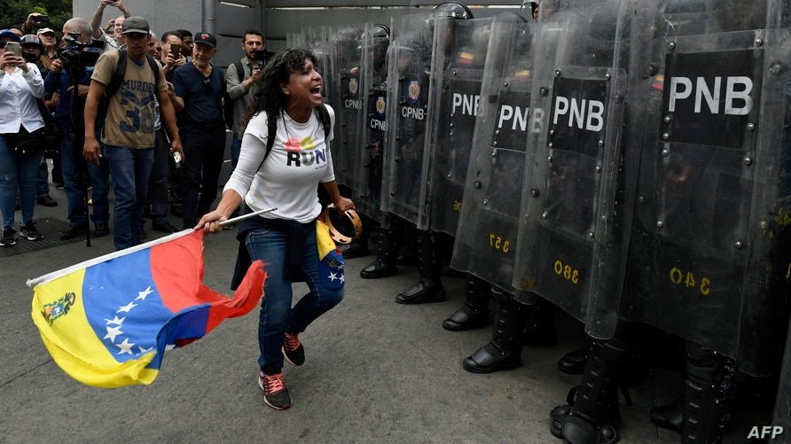 FILE - Opposition supporters confront Venezuelan security forces at the National Assembly in Caracas, Venezuela, March 10, 2020.