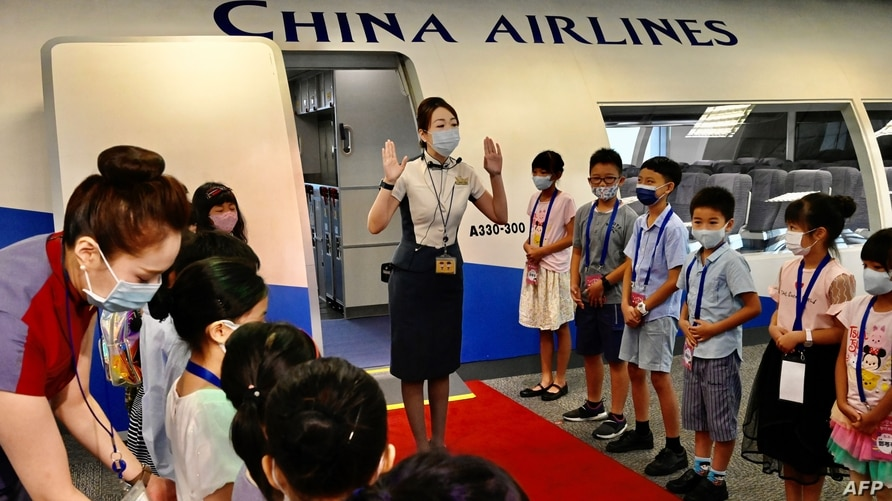 FILE - Flight attendants from Taiwan's China Airlines stage a 'flight to nowhere' event for children, at the China Airlines' campus in Taoyuan City, Taiwan, Aug. 8, 2020.