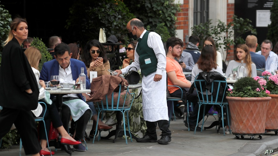 A waiter serves in a restaurant in Covent Garden in London, Sept. 22, 2020.