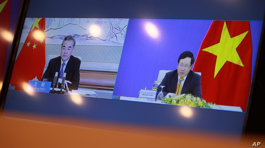 A TV screen shows Vietnamese Foreign Minister Pham Binh Minh and his Chinese counterpart Wang Yi during a virtual meeting on bilateral issues, in Hanoi, Vietnam, July 21, 2020.