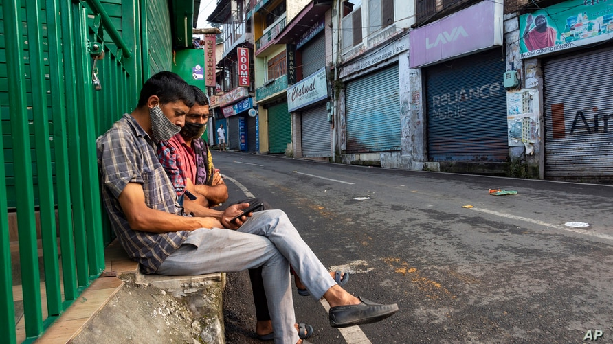 Day laborers wearing masks to protect against the coronavirus wait for work on a street in Dharmsala, India, Sept. 23, 2020.