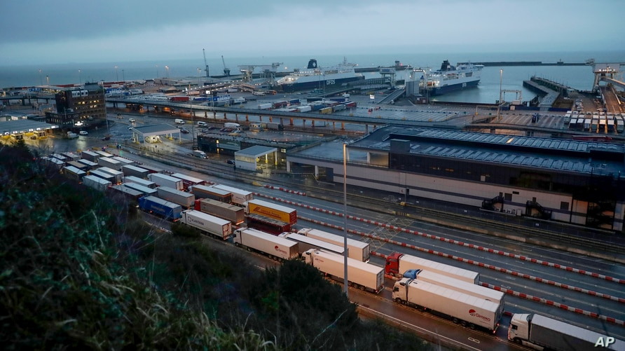 FILE - Trucks wait in lines to drive onto ferries at the Port of Dover, Britain, Feb. 1, 2020.