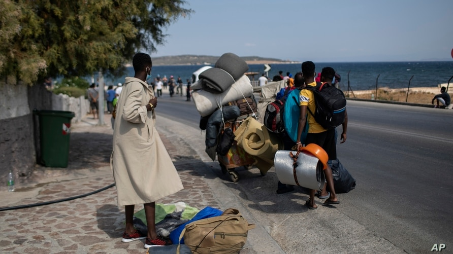 Migrants carrying their belongings, walk on a road near Mytilene town, on the northeastern island of Lesbos, Greece, Sept. 14, 2020.