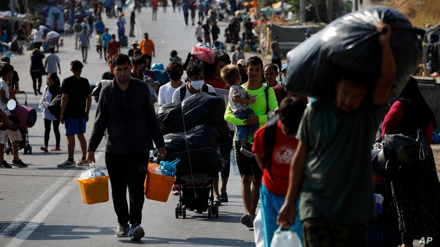 Migrants carry their belongings as they flee from Moria to the capital of Mytilene, on the northeastern island of Lesbos, Greece, Sept. 17, 2020.