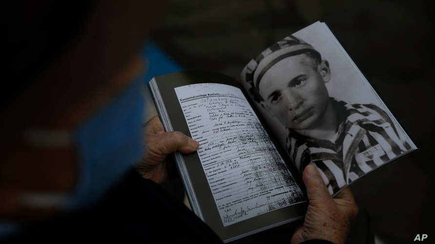FILE - Holocaust survivor Shalom Stamberg holds a book with a photo of himself in Auschwitz just before the start of an annual Holocaust memorial ceremony, in Haifa, Israel, April 21, 2020.