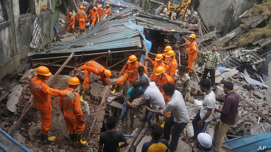 Rescuers look for survivors after a residential building collapsed in Bhiwandi in Thane district, a suburb of Mumbai, India, Sept.21, 2020.
