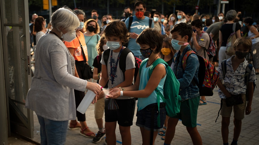 Students wearing face masks to prevent the spread of coronavirus disinfect their hands before entering their school in Barcelona, Spain.