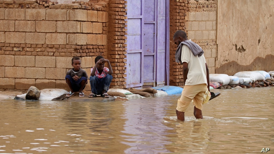 A man wades through a flooded street in the town of Shaqilab, about 25 kilometers southwest of the capital, Khartoum, Sudan, Aug. 31, 2020.
