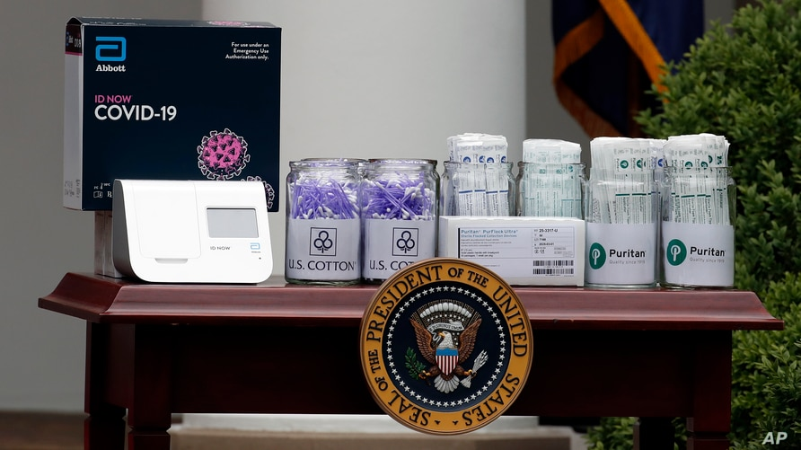 Materials for COVD-19 testing from Abbott Laboratories, U.S. Cotton, and Puritan are displayed as President Donald Trump speaks about the coronavirus during a press briefing in the Rose Garden of the White House, May 11, 2020, in Washington.