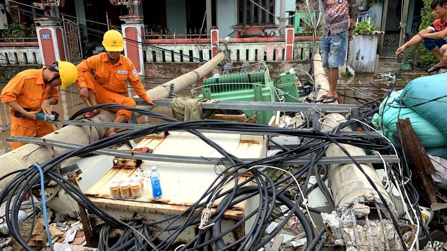 Workers clear toppled electric lines during the landfall of tropical storm Noul, in Hue, Vietnam, Sept. 18, 2020.