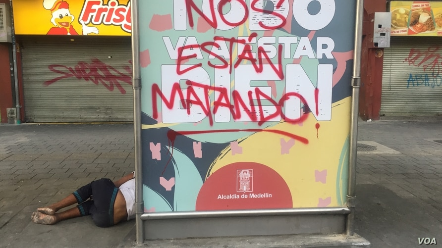 """Protesters' call of """"Nos Están Matando,"""" or """"They're Killing Us,"""" covers up Medellín government's coronavirus public relations campaign slogan in Medellín, Colombia. (Megan Janetsky/VOA)"""