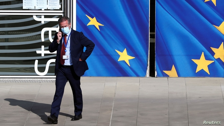 A man wearing a protective mask walks past the EU Commission headquarters amid the coronavirus outbreak, in Brussels, Belgium, Sept. 18, 2020.