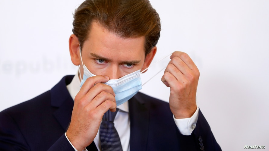 Austrian Chancellor Sebastian Kurz takes off a protective face mask as he arrives for a news conference amid a new coronavirus surge, in Vienna, Austria, Sept. 11, 2020.