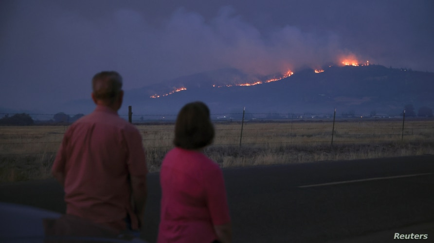 Local residents look at smoke and fire over a hill during wildfires near the town of Medford, Oregon, Sept. 9, 2020.
