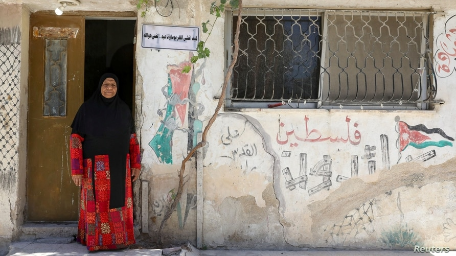 FILE - A Palestinian refugee woman living in Jordan wears a traditional Palestinian dress as she poses in front of her home at Al-Baqaa Palestinian refugee camp, near Amman, Jordan, June 16, 2020.