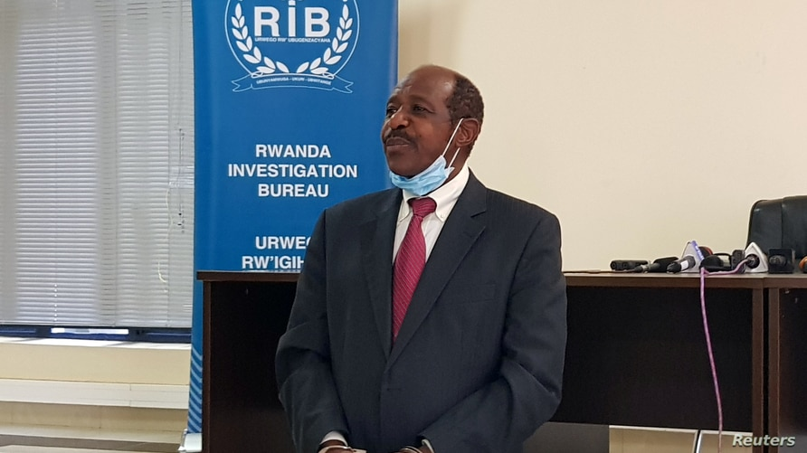 Paul Rusesabagina, the man who was hailed a hero in a Hollywood movie about Rwanda's 1994 genocide is paraded in handcuffs in front of media at the headquarters of Rwanda's Investigation Bureau, in Kigali, Aug. 31, 2020.