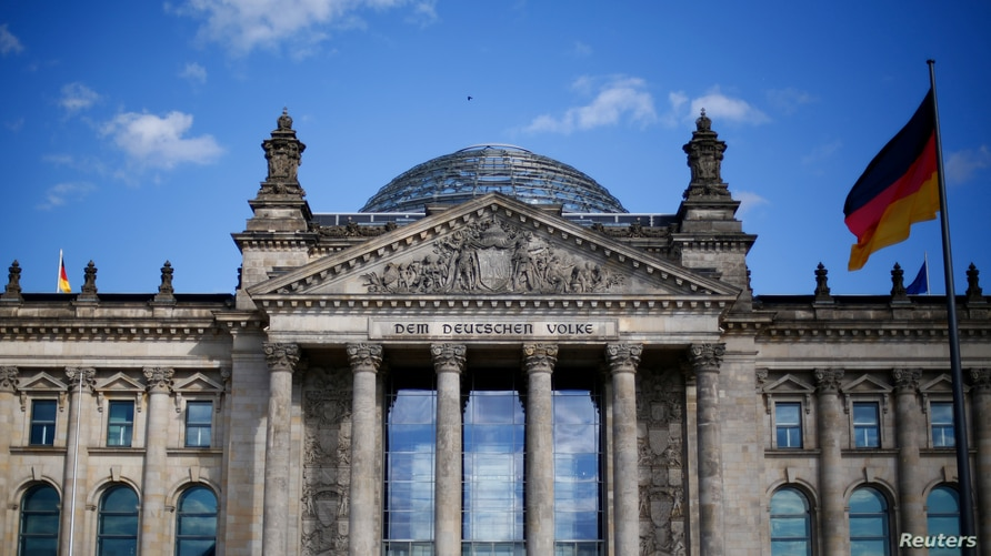 """FILE - A German flag flutters in front of the Reichstag building in Berlin, Germany, Sept. 6, 2020. The inscription on the building reads """"[Dedicated] to the German people."""""""