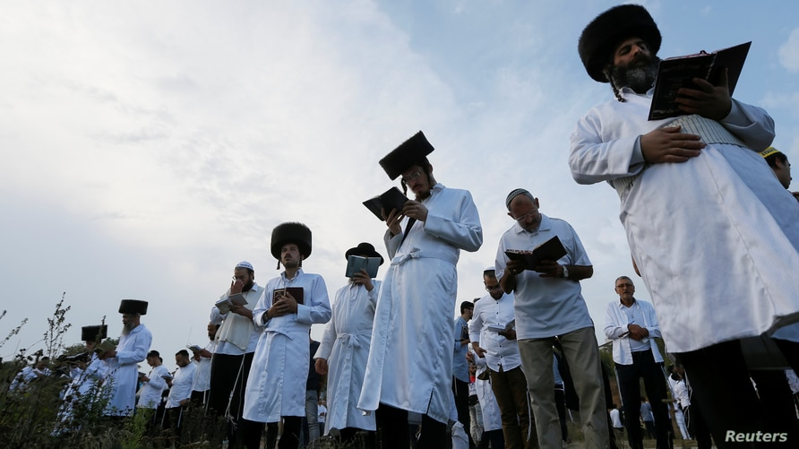 FILE - Orthodox Jewish pilgrims pray on a bank of a lake near the tomb of Rabbi Nachman of Breslov during the celebration of the Rosh Hashanah holiday, the Jewish New Year, in Uman, Ukraine, Sept. 21, 2017.