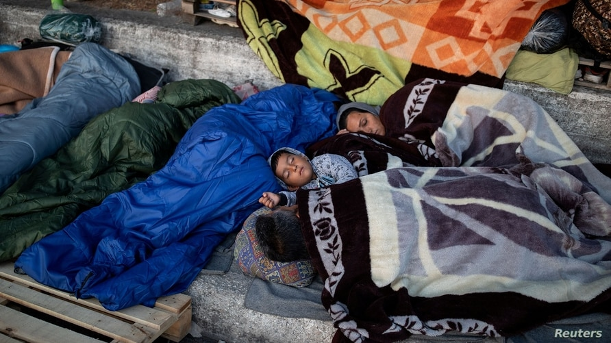 Refugees and migrants from the destroyed Moria camp sleep on the side of a road, on the island of Lesbos, Greece, Sept. 13, 2020.
