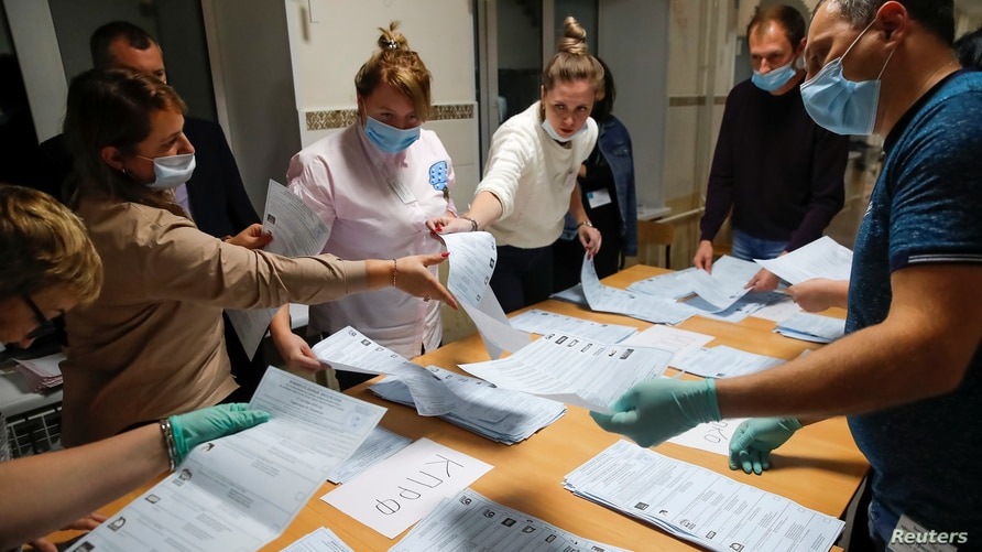Members of a local electoral commission count ballots at a polling station after polls closed for the municipal elections in Tomsk, Russia, Sept. 13, 2020.