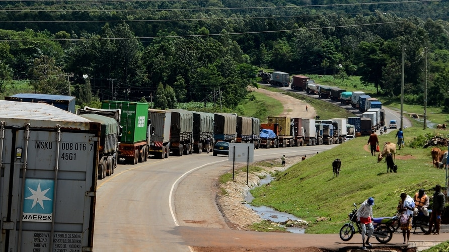 Trucks wait in a line on the road to enter Uganda in Malaba, a city bordering with Uganda, western Kenya, on April 29, 2020. -…