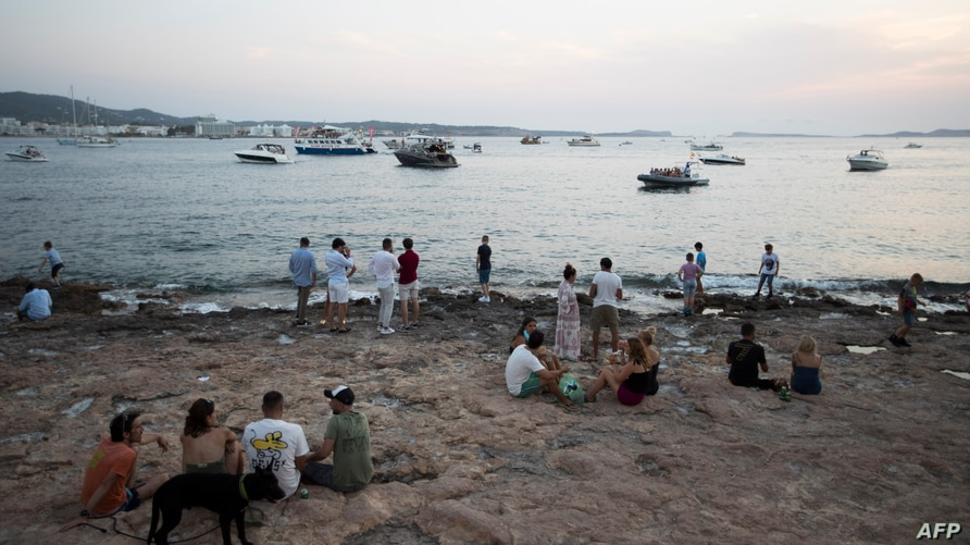 "People contemplate the sunset in front of the terrace bar ""Cafe del Mar"" in Sant Antoni de Portmany, Ibiza, on July 30, 2020. -…"