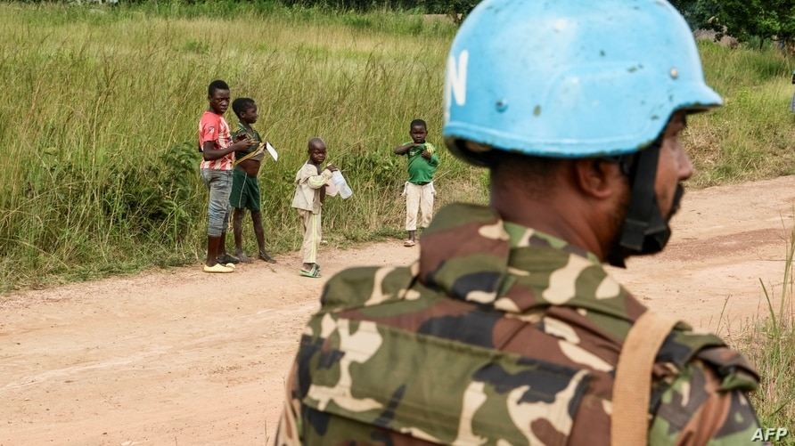 Children look at an United Nations (UN) Bangladeshi soldier part of MINUSCA (United Nations Multidimensional Integrated…