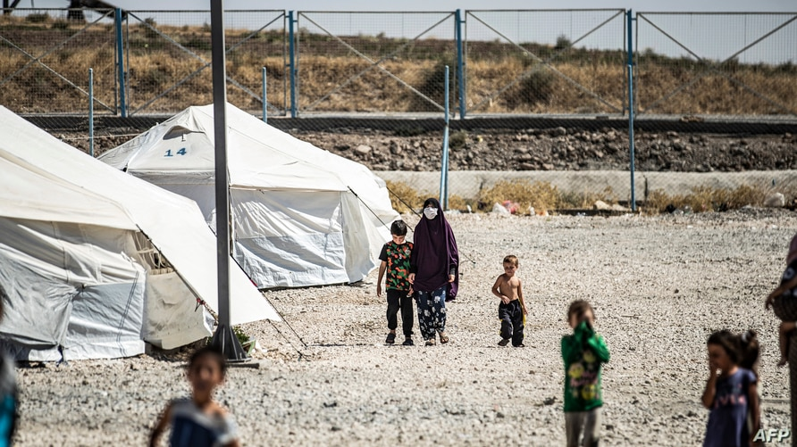 A woman clad in mask due to the COVID-19 coronavirus pandemic walks next to a child by tents at Camp Roj, housing family…