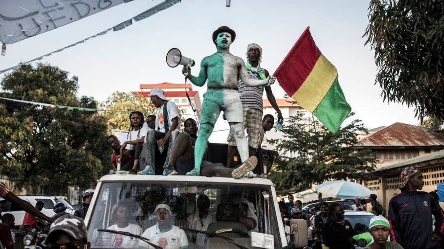 Supporters of main opposition candidate, Cellou Dalein Diallo stand on a van at a campaign rally in Conakry on October 14, 2020…