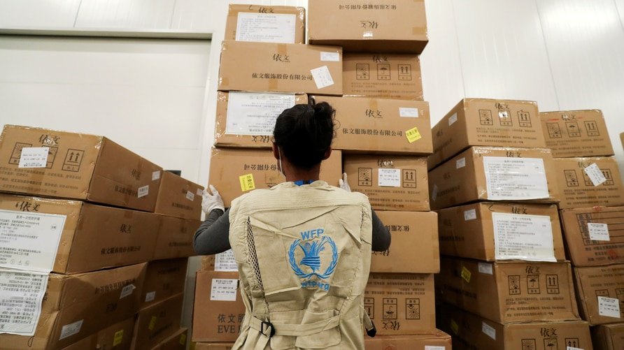 FILE - A World Food Program worker arranges relief packages for humanitarian aid for Africa to combat the outbreak of the coronavirus disease, at the Bole International Airport in Addis Ababa, Ethiopia, April 14, 2020.