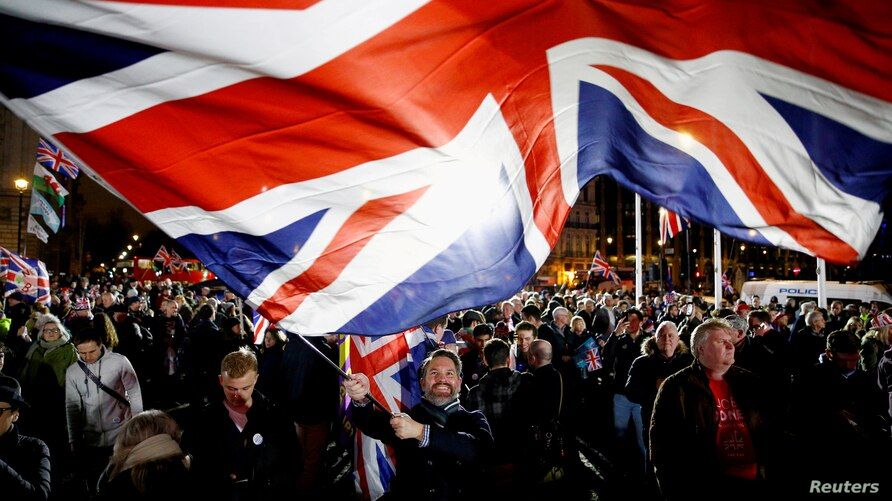 FILE - A man waves a British flag on Brexit day in London, Britain, Jan. 31, 2020.