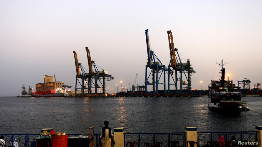 FILE PHOTO: A man stands opposite the modern port at the harbour in Port Sudan at Red Sea State February 24, 2014. REUTERS…