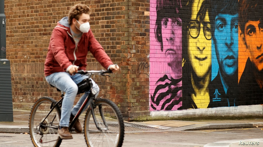 A man wearing a protective mask rides a bike past a mural depicting members of The Beatles, amid the outbreak of the…