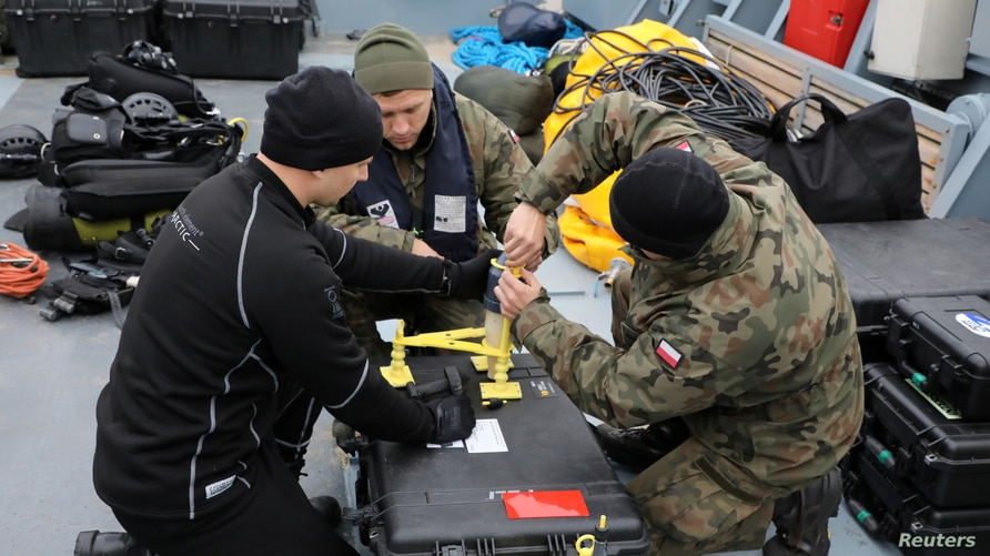 FILE - Navy divers from the 12th Minesweeper Squadron of the 8th Coastal Defense Flotilla take part in an operation to defuse the largest unexploded World War II Tallboy bomb ever found in Poland, in Swinoujscie, Oct. 12, 2020.