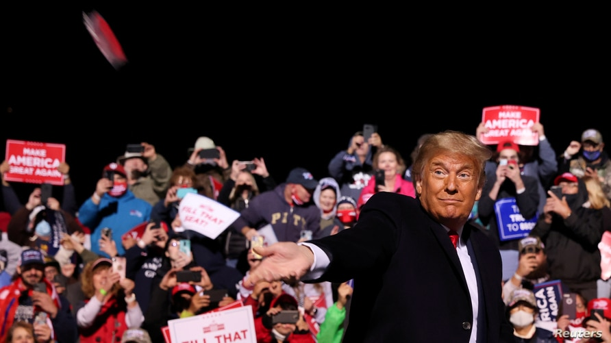 U.S. President Donald Trump throws face masks to the crowd as he arrives to hold a campaign rally at John Murtha Johnstown.