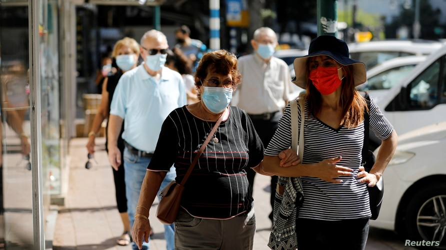 People wearing protective face masks walk down a main street as Israel began easing a second nationwide coronavirus disease …