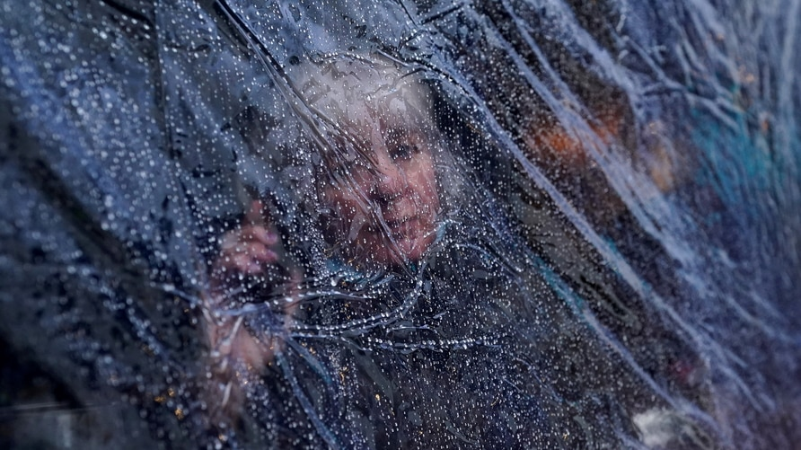 Raindrops are seen on outdoor protective plastic sheeting surrounding a woman on her phone at a cafe dining area as the…