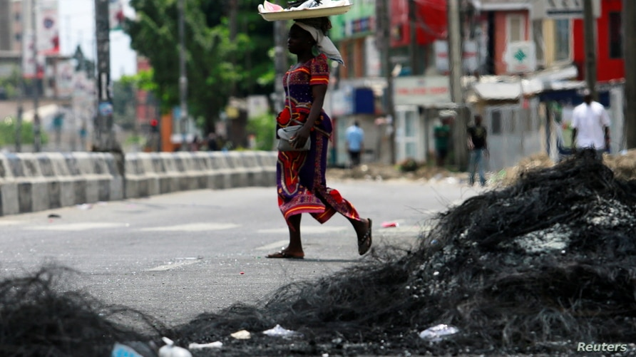 A woman walks past the remains of a burnt barricade in Surulere area of Lagos, Nigeria October 23, 2020. REUTERS/Afolabi Sotunde