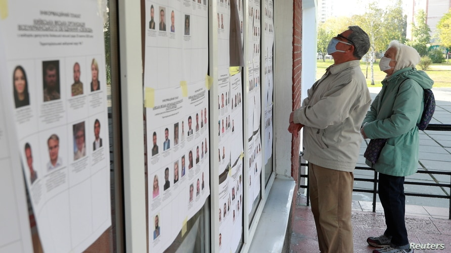 Voters wearing protective face masks stand in front of an information board outside a polling station during local elections…