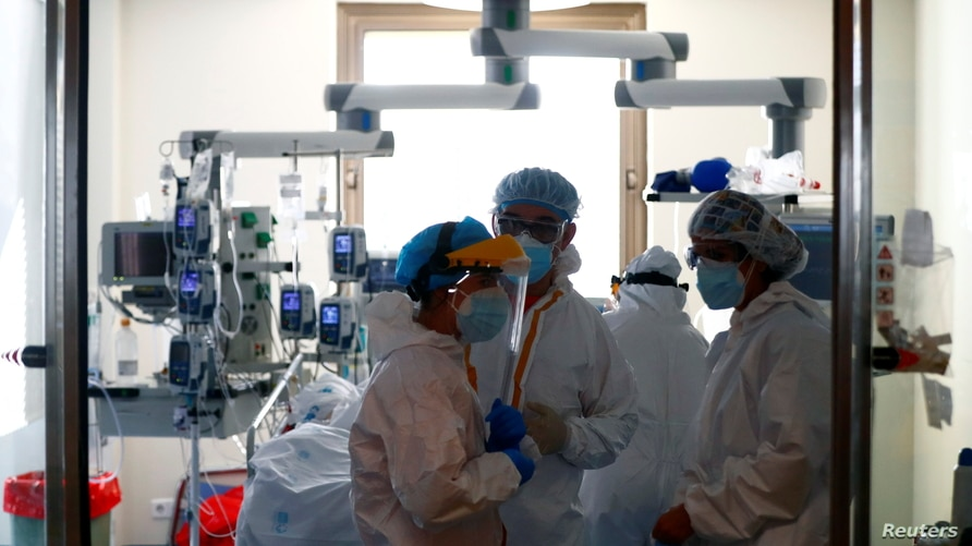 Medical workers talk before taking care of a patient infected with COVID-19 at the intensive care unit (ICU).