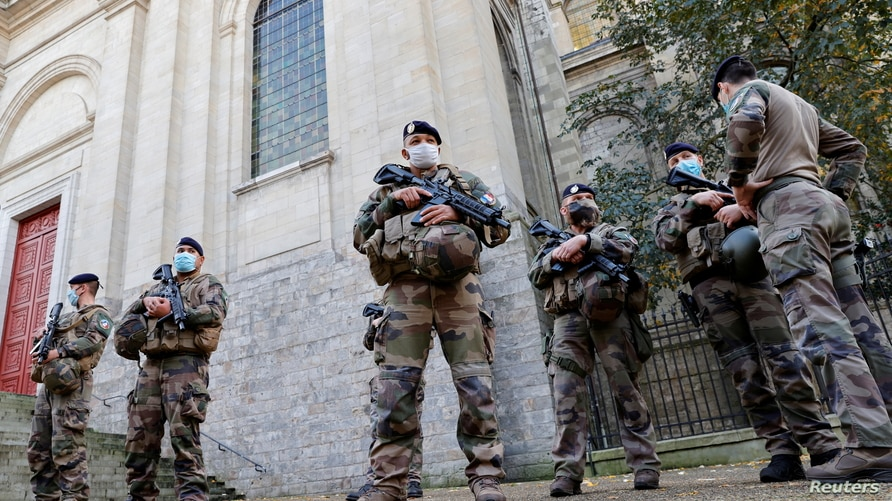 "French soldiers, part of France's national security alert system ""Sentinelle"", patrol near the Cathedral in Arras."