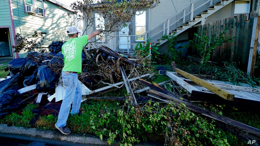 Caleb Cormier moves debris after Hurricane Delta moved through, Saturday, Oct. 10, 2020, in Lake Charles, La. Delta hit as a…