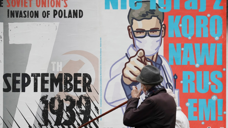 A man passing by a poster warning against neglecting COVID-19 symptoms, in Warsaw, Poland, on Friday, October 16, 2020. Poland…