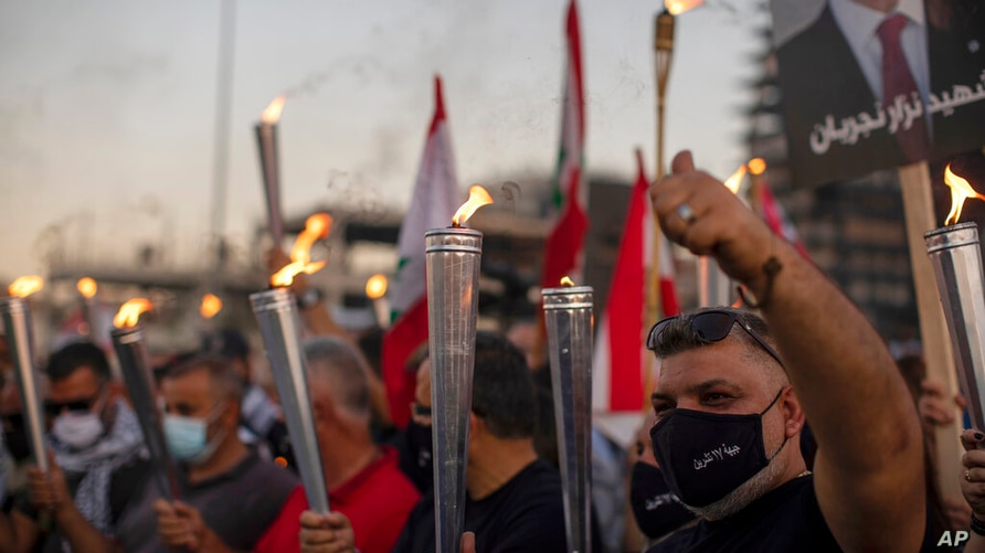 "Anti-government protesters hold up torches as they lit a giant flame over a metal statue that reads in Arabic: ""October 17,…"