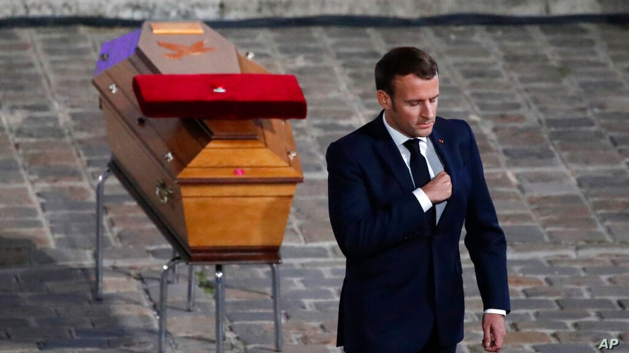 French President Emmanuel Macron leaves after paying his respects by the coffin of slain teacher Samuel Paty in the courtyard…