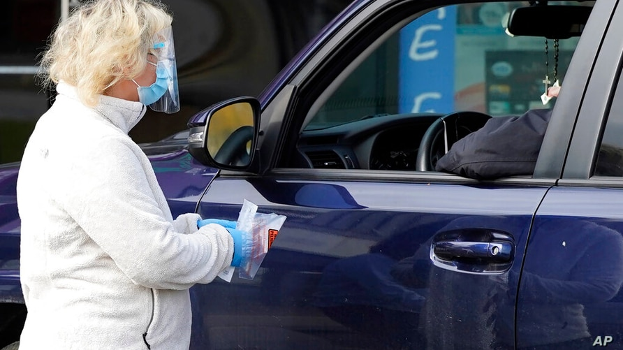 Exam Corp Lab employee, left, conducts a COVID-19 test at the parking lot of the facility in Niles, Ill., Wednesday, Oct. 21,…