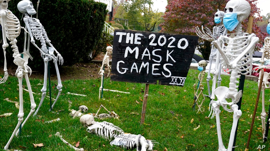 FILE - In this Oct. 22, 2020, file photo, coronavirus-themed Halloween decorations are displayed on a lawn in Tenafly, N.J. In…